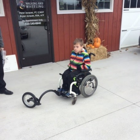 "A ""Free Wheel"" add on to this young man's manual wheelchair."